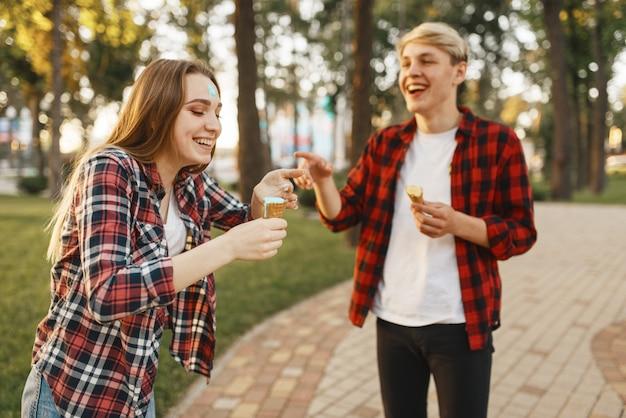 Casal apaixonado se divertindo com sorvete no parque