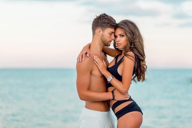 Casal apaixonado se divertindo em uma praia paradisíaca tropical, usando maiô estiloso