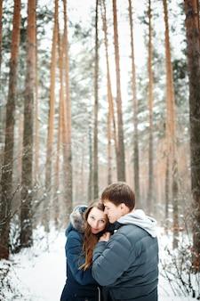 Casal apaixonado se divertindo na floresta de inverno