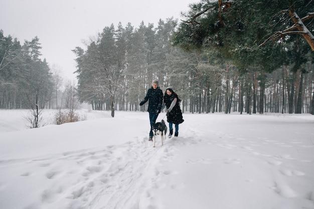 Casal apaixonado se divertir com o cão husky no dia frio de inverno nevado