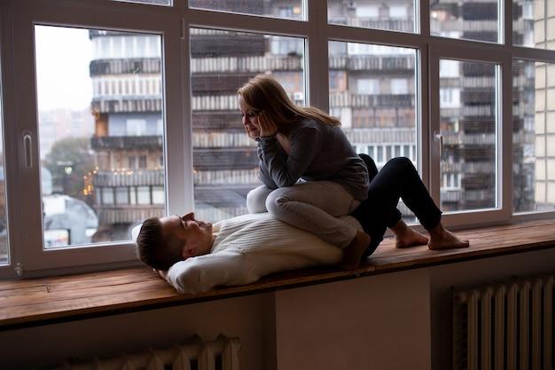 Casal apaixonado se divertir perto da janela em casa