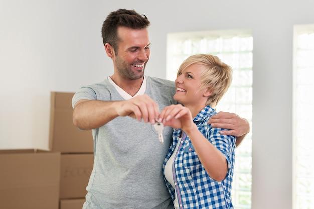Casal apaixonado segurando a chave da nova casa