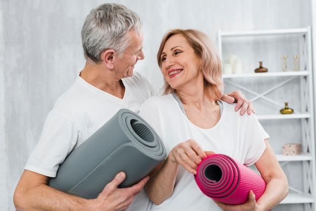 Casal apaixonado, segurando o tapete de ioga, olhando um ao outro