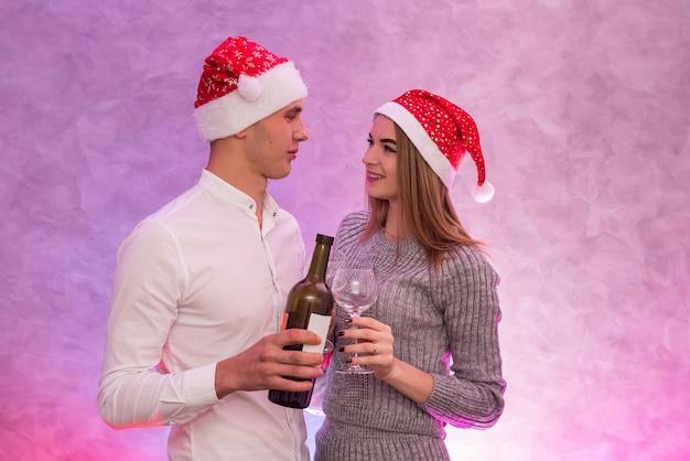 Casal apaixonado segurando uma garrafa de vinho e copos comemorando o dia dos namorados em estúdio