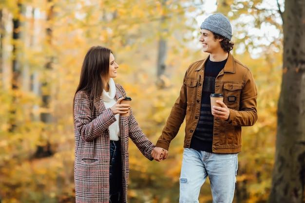 Casal apaixonado segurando xícaras de chá ou café e de mãos dadas