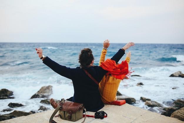 Casal apaixonado senta-se no cais e olha para o mar