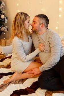 Casal apaixonado sentado ao lado de uma árvore de natal e curtindo momentos românticos. lindo casal se abraçando perto da árvore de natal. jovem casal passando o natal juntos.