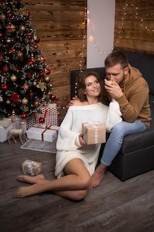 Casal apaixonado, sentado ao lado de uma árvore de natal em casa