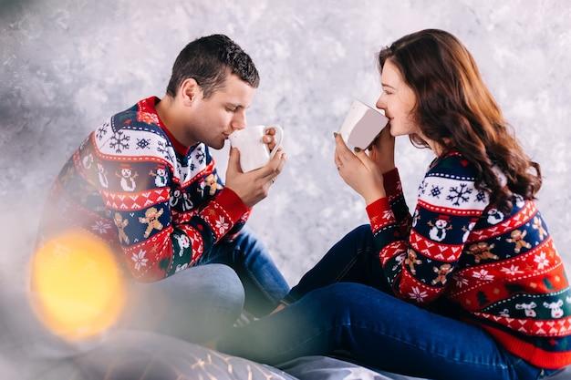 Casal apaixonado, sentado e bebendo uma bebida quente no fundo da parede. reflexo de lente.