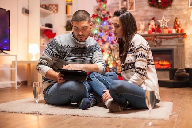 Casal apaixonado, sentado em frente a árvore de natal, olhando no computador tablet.