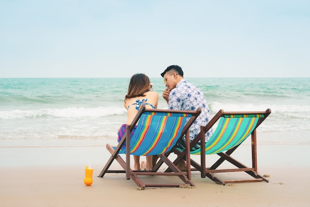 Casal apaixonado, sentado nas cadeiras de praia praia tropical nas férias de verão