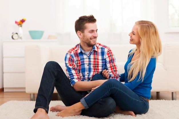 Casal apaixonado sentado no chão da sala de estar