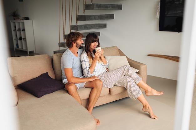 Casal apaixonado, sentado no sofá acolhedor