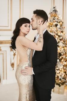 Casal apaixonado sexy celebrando o natal juntos mulher atraente em ouro vestido de noite e han ...