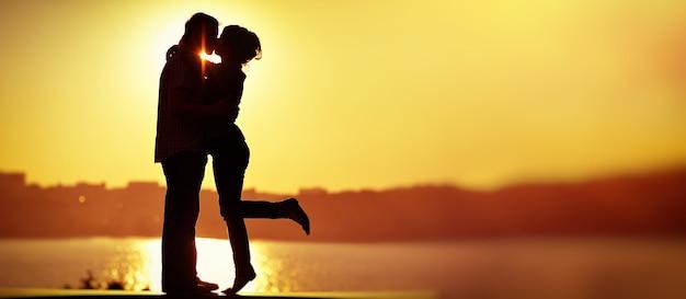 Casal apaixonado silhueta de luz de fundo no pôr do sol laranja do lago