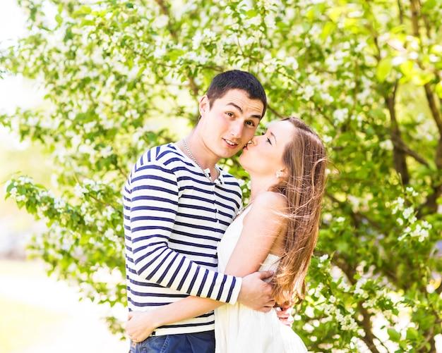 Casal apaixonado sob galhos florescendo dia de primavera. jovem adulto morena homem e mulher beijando no jardim de árvores de maçã ou cereja de flor fresca. beijo doce