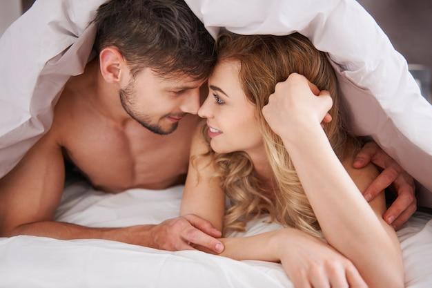 Casal apaixonado sob o edredom