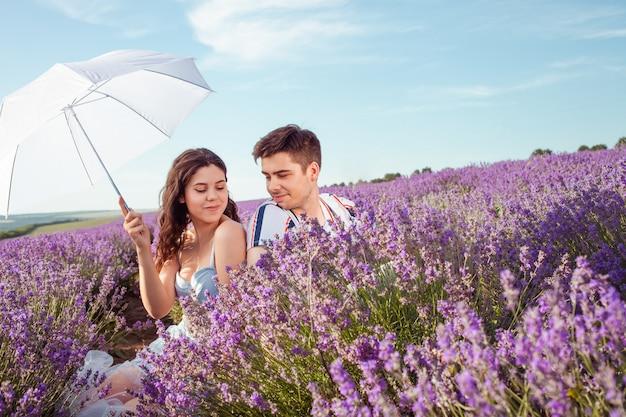 Casal apaixonado sob um guarda-chuva branco em um campo de lavanda