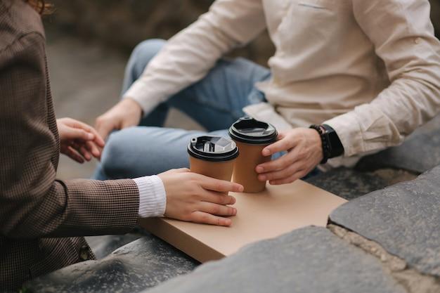 Casal apaixonado sorridente, sentado na escada ao ar livre e segurando uma xícara de café