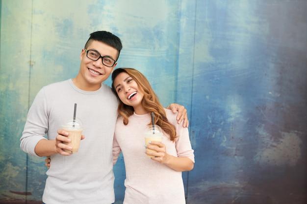 Casal apaixonado sorrindo alegremente segurando milkshakes