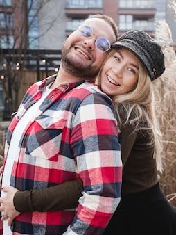 Casal apaixonado sorrindo ao ar livre. casal bonito de descolados está caminhando no parque primavera. lindo dia de sol. caminhando pelas ruas da cidade, noite de primavera. conceito de lua de mel.
