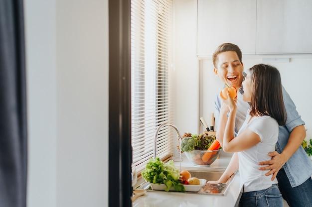 Casal apaixonado, sorrindo e se divertir enquanto cozinha na cozinha