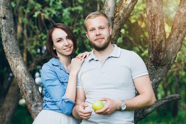Casal apaixonado tem um descanso no pomar de verão