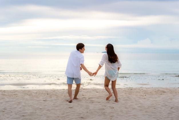 Casal apaixonado tendo momentos românticos de ternura correndo e segurando a mão na praia entre o pôr do sol