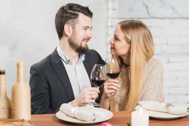 Casal apaixonado tinindo com copos no jantar