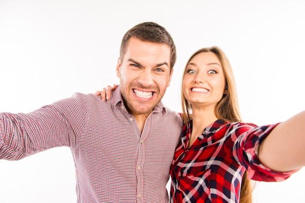 Casal apaixonado tirando selfie cômico