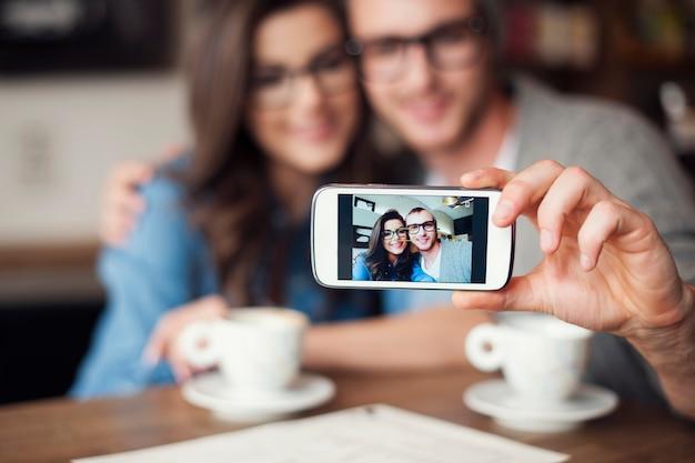 Casal apaixonado tirando uma selfie em um café