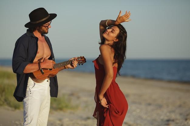 Casal apaixonado tocando violão e dançando na praia