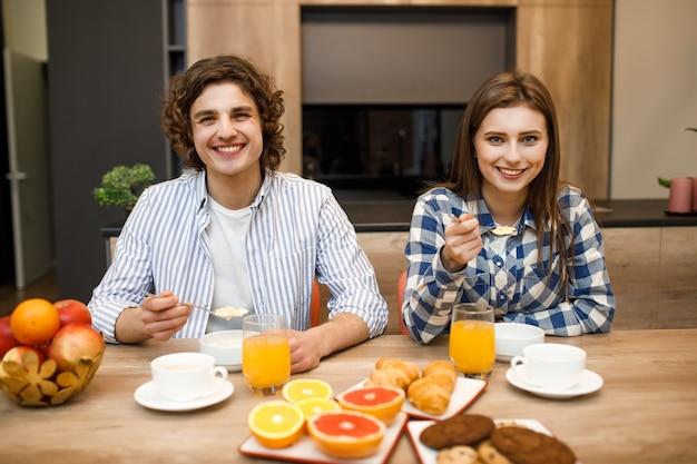 Casal apaixonado tomando café da manhã juntos na cozinha