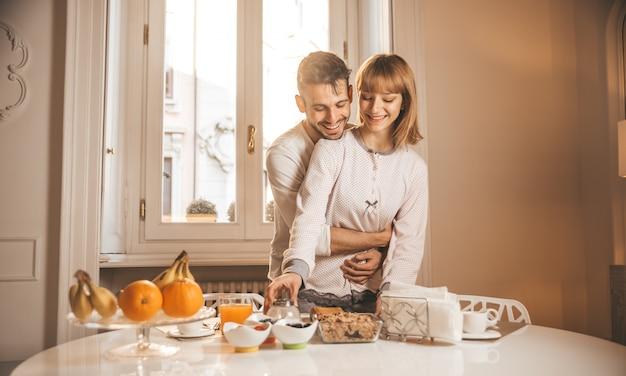 Casal apaixonado tomando café da manhã na cozinha em casa e se divertindo.