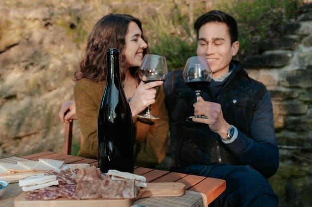 Casal apaixonado tomando um aperitivo ao ar livre no jardim degustando vinho tinto