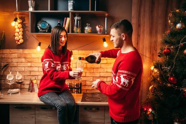 Casal apaixonado, um homem derrama champanhe em uma taça de mulher, uma romântica celebração de natal. homem e mulher celebram o natal juntos