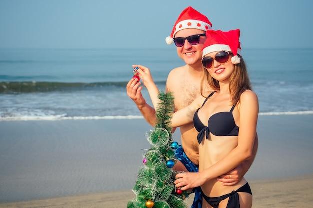 Casal apaixonado usando um chapéu de papai noel e decorando uma árvore de natal na praia