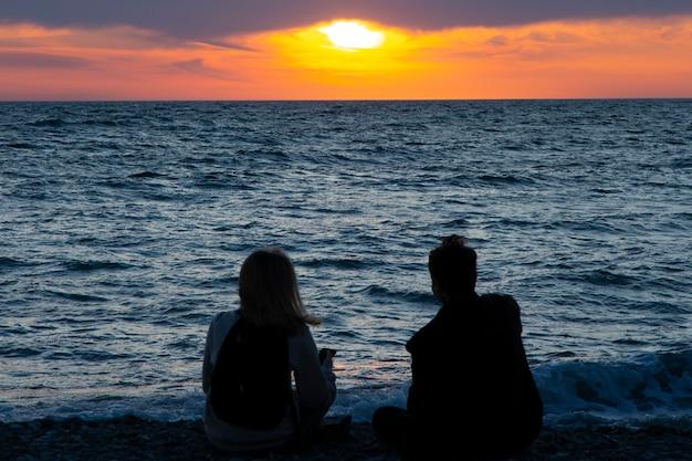 Casal apaixonado, vendo o pôr do sol juntos na praia, viaja nas férias de verão. pessoas silhueta por trás sentado, apreciando a vista do mar do sol em férias de destino tropical. casal romântico na praia