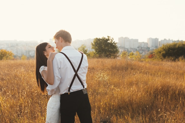 Casal apaixonado, vestido de branco beijando ao ar livre