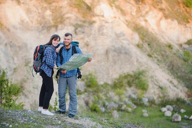 Casal apaixonado viaja nas montanhas com um mapa e binóculos