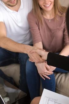 Casal apertando as mãos com corretor de imóveis. renovação de imóveis e residências