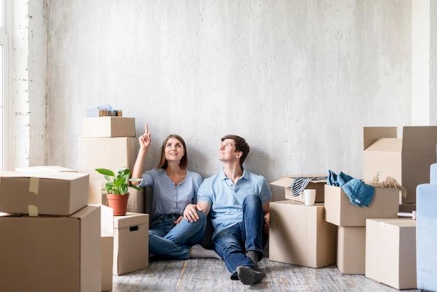 Casal apontando para cima enquanto faz as malas para mudar de casa