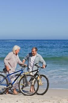 Casal aposentado com suas bicicletas na praia