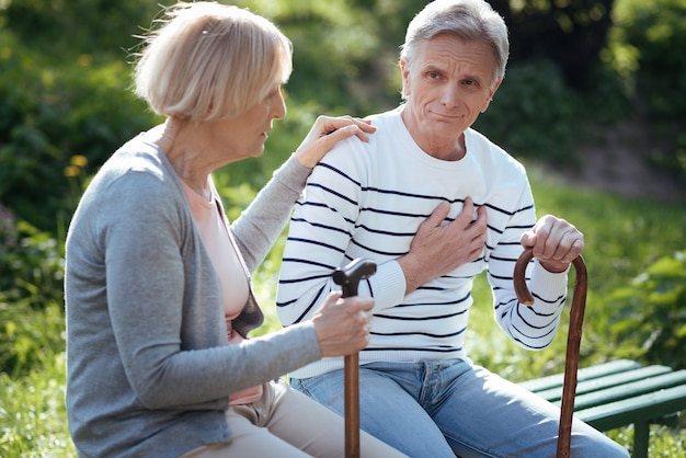 Casal aposentado concentrado e solidário se sentindo mal e se apoiando enquanto está sentado no banco ao ar livre