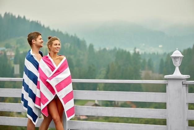 Casal apreciando a paisagem, em pé perto da piscina durante o dia.