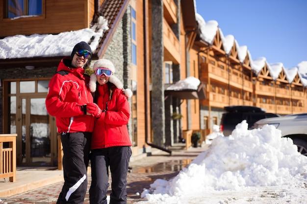 Casal apreciando a vista de casas e chalés em uma estação de esqui