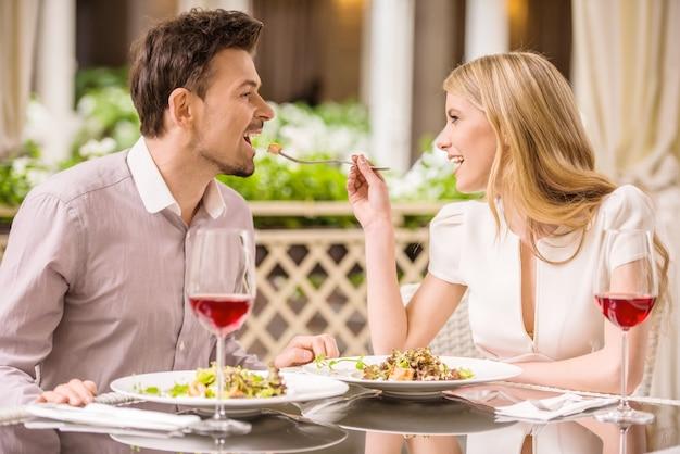 Casal aproveitando a refeição no restaurante e bebendo vinho.