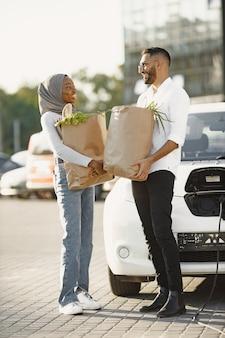 Casal árabe africano fica com mantimentos perto de carro elétrico. carregando carro elétrico no posto de gasolina elétrico