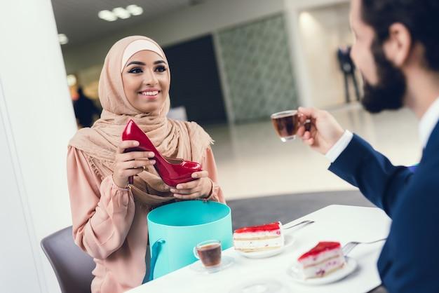 Casal árabe está bebendo chá no shopping