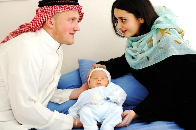 Casal árabe muçulmano com novo bebê em casa